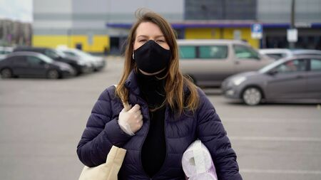 Woman in face protective mask with goods after supermarket. covid-19 coronavirus
