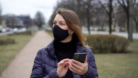 Woman in face protective mask in a city with mobile phone. covid-19 coronavirus Stock fotó