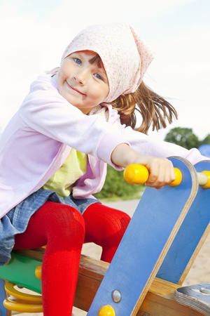small girl playing on childrens playground