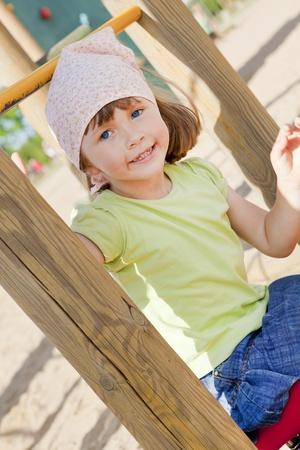 klein meisje spelen op speelplaats voor de kinderen Stockfoto