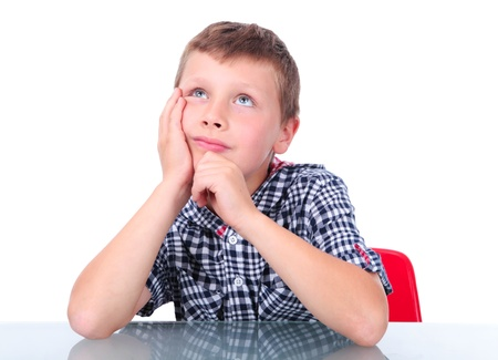 small boy sitting near table and thinking