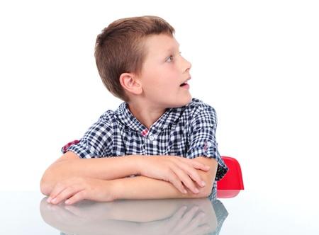 verbaasde jongen zitten in de buurt tafel en kijken naar links