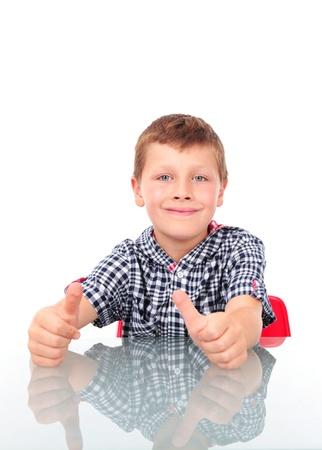 jonge jongen zitten in de buurt tafel en het tonen van OK teken Stockfoto