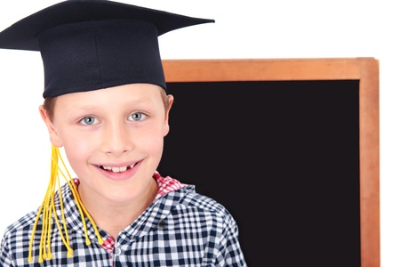 kleine afgestudeerde jongen in cap met bord op de achtergrond