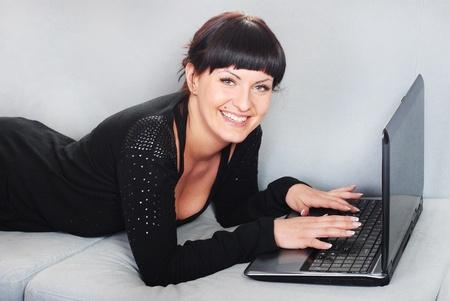 glimlachende brunette vrouw werken met laptop in huis Stockfoto