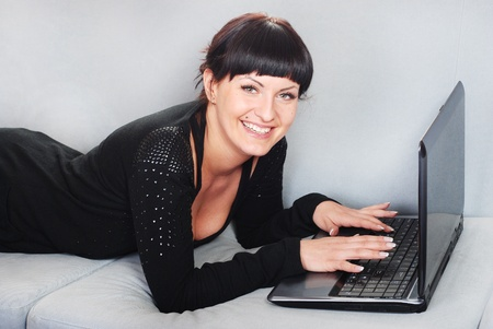 smiling brunette woman working with laptop in home