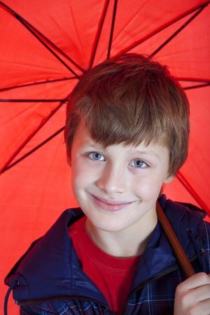 portret van jongen die rode paraplu Stockfoto