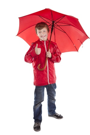 portrait of boy holding red umbrella over white background Stock Photo