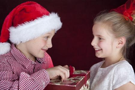 kerst jongen geven aanwezig om lachende meisje
