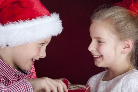 christmas boy giving present to smiling girl