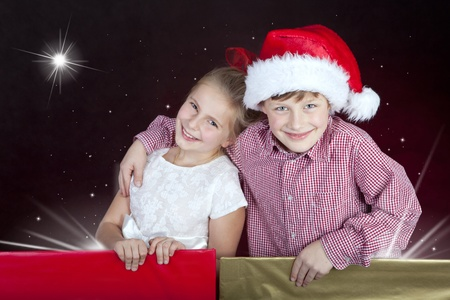 girl and boy in christmas hat in present boxes Stock Photo