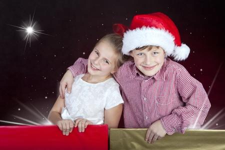 meisje en jongen in kerstmis hoed in het huidige dozen