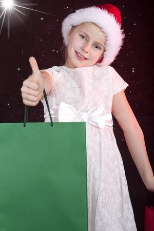 lachend meisje in kerstmis hoed bedrijf boodschappentassen Stockfoto