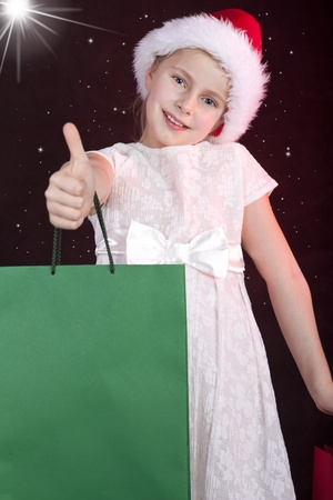 smiling girl in christmas hat holding shopping bags Stock Photo