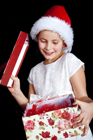 smiling girl holding christmas present over dark