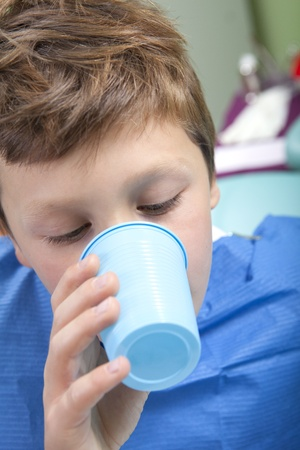 Jonge jongen drinkwater na tandheelkundige ingreep