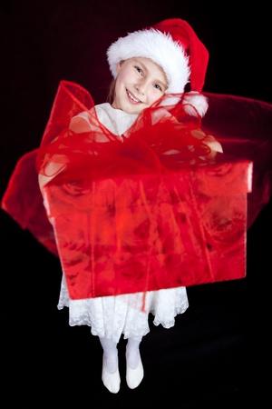 smiling girl holding christmas present over dark
