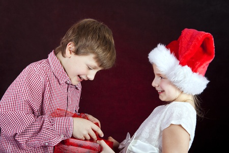 christmas girl giving present to surprised boy over dark