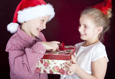 christmas boy giving present to smiling girl over dark
