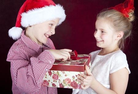 kerst jongen geven aanwezig om lachende meisje op donkere