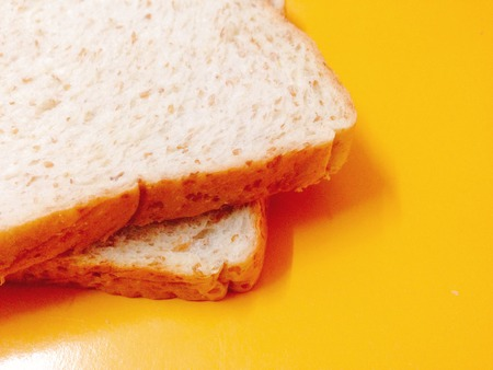 Fresh whole wheat bread placed on a yellow background. Stock Photo