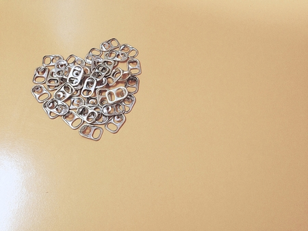 Recycling aluminum lid can be used to make artificial legs. Lay a heart shaped background.