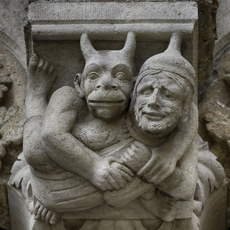 Devil and man carved in stone