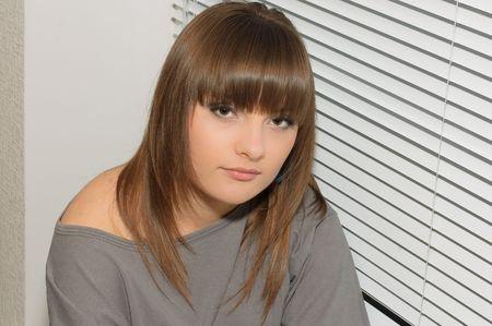 Young brunette sitting on the windowsill photo