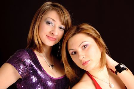 Two pretty young girlfriends in a bright dress on a black background photo