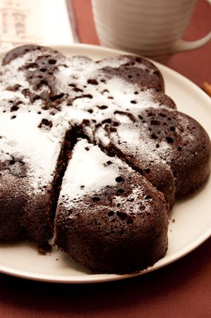 chocolate cake with icing sugar and a cup of coffee on a brown tablecloth