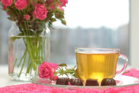 Glass cup with green tea, chocolates and pink roses on the table by the window photo
