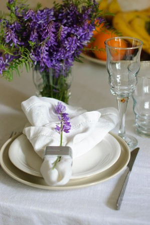Table with elegant setting, on the white tablecloth with purple flowers and fruits