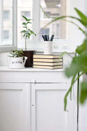 A stack of books, flowers and pencils in a cozy white verandah photo