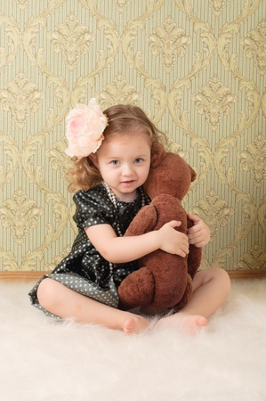 Little girl dressed as a retro doll sits on the floor with a toy photo