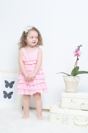 Girl in a pink dress in a white room
