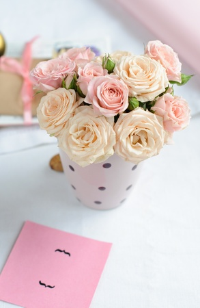 boeket van delicate roze rozen in een cup op de tabel
