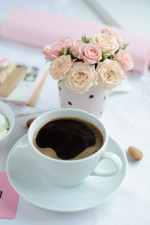 cup of coffee and a bouquet of delicate pink roses on the table in the morning photo