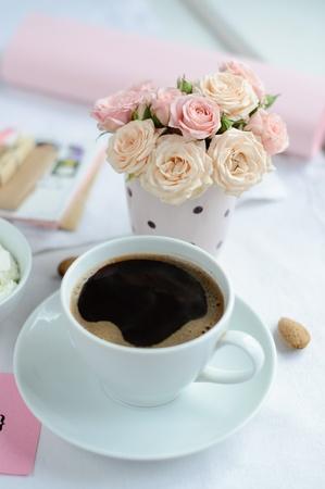 kopje koffie en een boeket van delicate roze rozen op de tafel in de ochtend