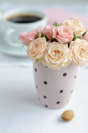 bouquet of delicate pink roses in a cup on the table photo