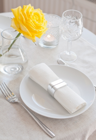 dining table: An elegant dining table setting with a white cloth and a yellow rose