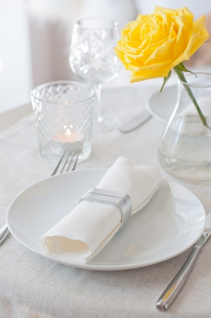 linens: An elegant dining table setting with a white cloth and a yellow rose