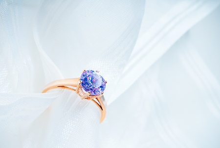 golden engagement ring with a stone on a white fabric photo