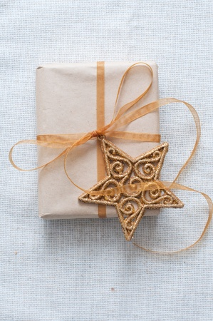 Christmas gift with a golden star, tied with ribbon photo