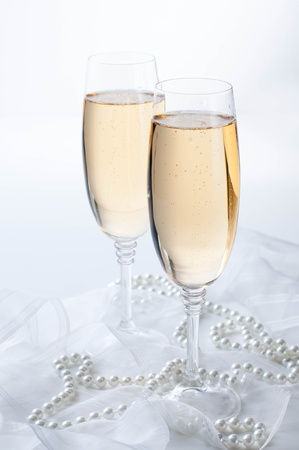champagne glasses: Two glasses of champagne on white fabric