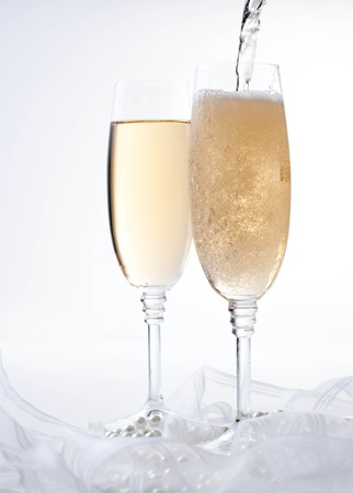 champagne flutes: Champagne is pouring into a glass on a white background