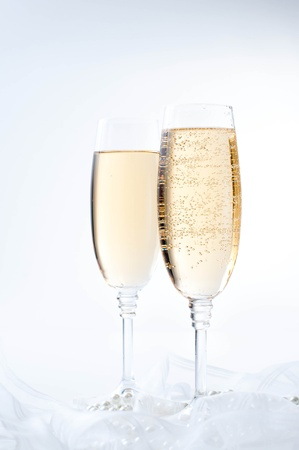 champagne flutes: Two glasses of champagne on white fabric
