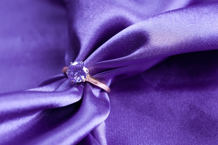 golden engagement ring with a gem on silk fabric photo