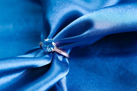 blue silk: golden engagement ring with a gem on silk fabric Stock Photo