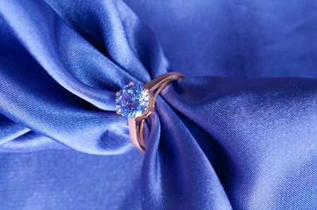 golden engagement ring with a gem on silk fabric Stock Photo - 12056429