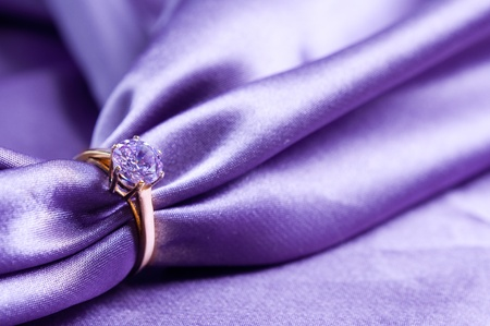 purple love: golden engagement ring with a gem on silk fabric Stock Photo